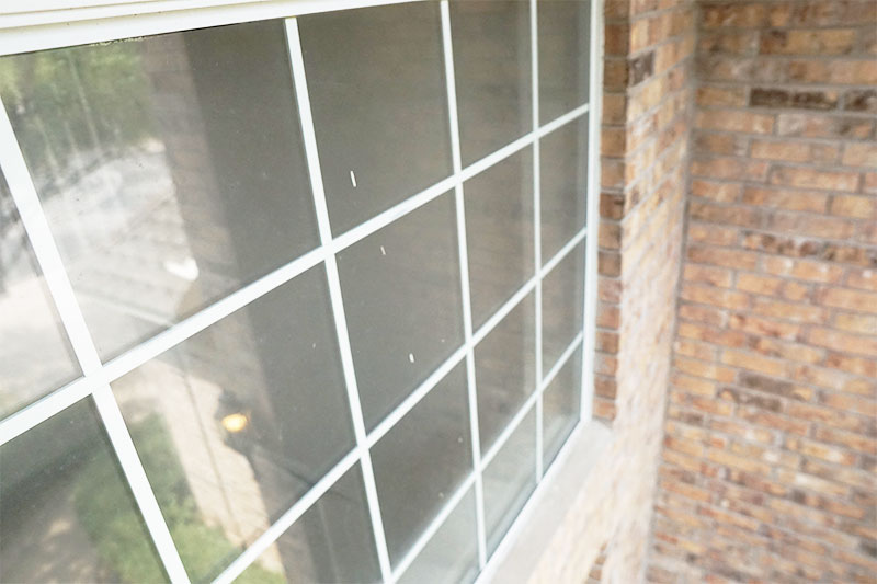 Window Washing Company In Austin TX displaying a before image of a dirty window